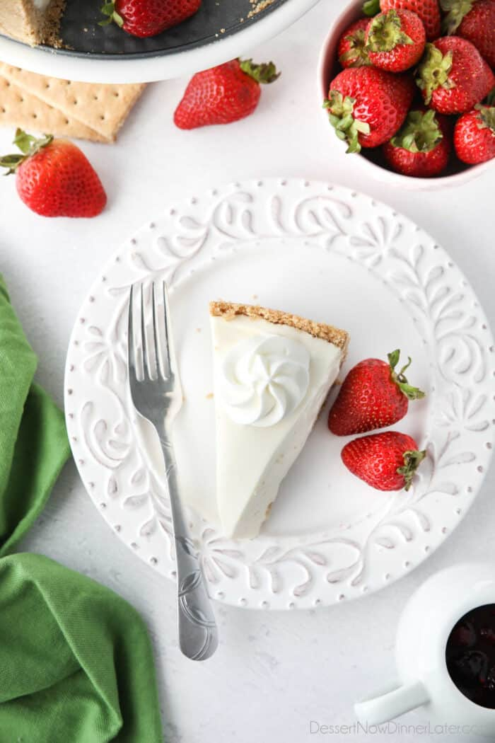 Slice of no bake cheesecake topped with a swirl of whipped cream.
