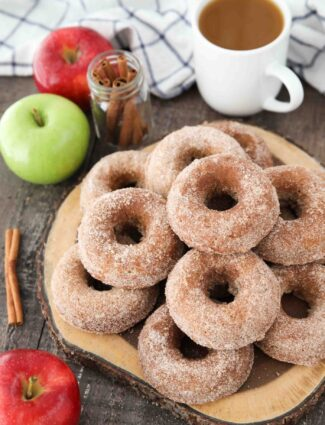 Baked Apple Cider Donuts stacked on top of a wooden cutting board with a cup of cider, fresh apples, and cinnamon sticks on the side.